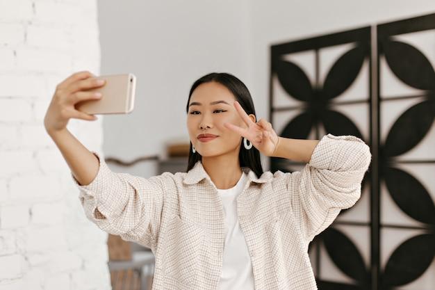 Mooie brunette vrouw in beige jas en wit t-shirt neemt selfie en toont v-teken