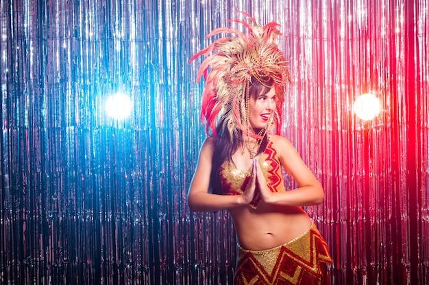 Mooie brunette vrouw in cabaret pak en hoofdtooi met natuurlijke veren en strass steentjes