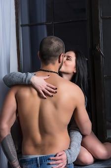 Mooie brunette vrouw in een gebreide jurk zit op de vensterbank en kuste haar man met blote borst en getatoeëerde handen