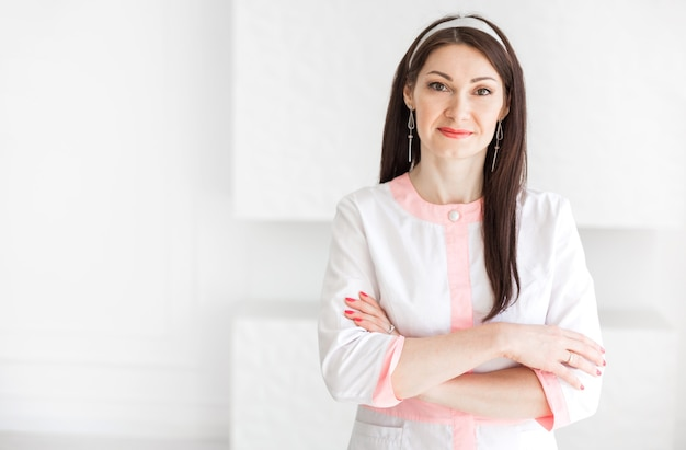 Mooie brunette vrouw in een wit medisch pak poseren tegen een achtergrond van een witte muur met gekruiste armen.