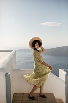 Mooie brunette vrouw in gebloemde jurk kijkt naar voren, houdt schipper vast en beweegt op balkon met uitzicht op de oceaan