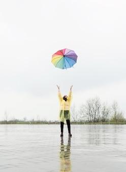 Mooie brunette vrouw in gele regenjas die kleurrijke paraplu in de regen gooit