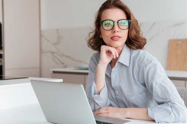 Mooie brunette vrouw in glazen houdt haar kin en kijkt opzij zittend op de werkplek