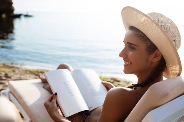 Mooie brunette vrouw in hoed leesboek, liggend op het strand