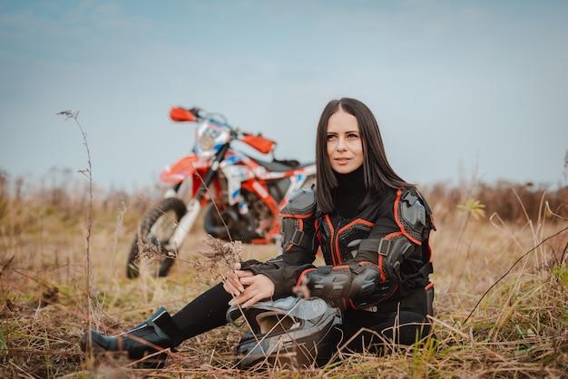 Mooie brunette vrouw in motorfiets outfit.