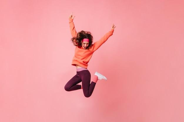 Mooie brunette vrouw in roze sporthoofdband en trainingspak springt op geïsoleerde roze muur