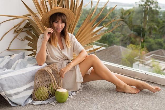 Mooie brunette vrouw in strooien hoed en linnen jurk poseren op terras over droog palmblad. verse kokosnoten.