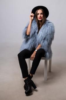 Mooie brunette vrouw in trendy blauwe bontjas en zwarte hoed poseren op grijze muur.