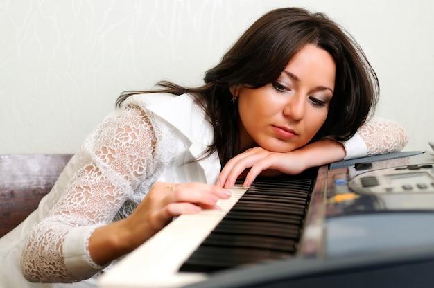 Mooie brunette vrouw in witte blouse zit en speelt thuis op piano klavier.