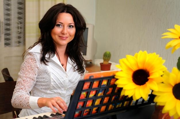 Mooie brunette vrouw in witte blouse zit en speelt thuis op synthesizer.