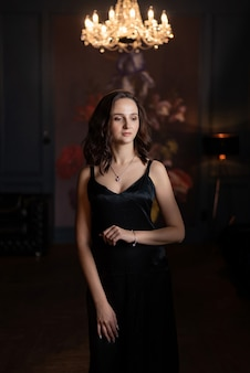 Mooie brunette vrouw in zwarte zijden jurk poseren in een designkamer met een kroonluchter