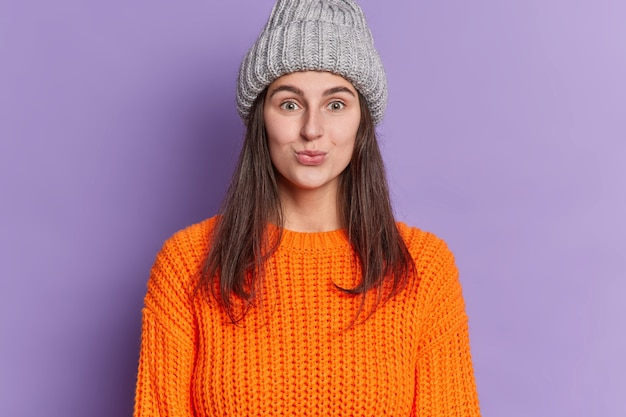 Mooie brunette vrouw kijkt met grappige uitdrukking pruilt lippen draagt gebreide grijze muts oranje trui geniet winterseizoen.