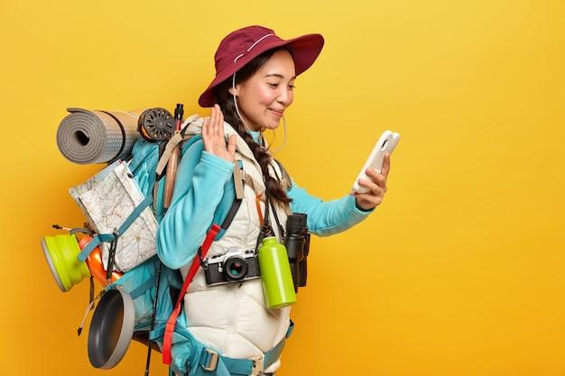 Mooie brunette vrouw maakt videogesprek, golven met palm op smartphone camera, maakt gebruik van moderne technologie om in contact te blijven met vrienden tijdens expeditie