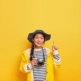 Mooie brunette vrouw met aziatische uitstraling, neemt foto tijdens wandeltocht met retro camera, draagt gestreepte trui, hoed en regenjas, wijst naar boven met wijsvinger, geïsoleerd over gele muur