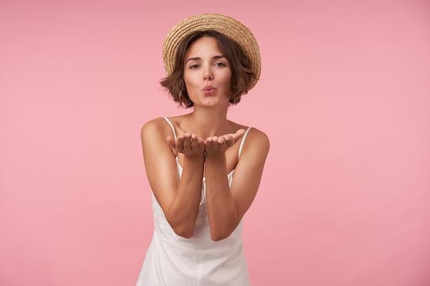 Mooie brunette vrouw met casual kapsel verhogen palmen en blazen lucht kus, witte zomerjurk en strooien hoed dragen tijdens het poseren