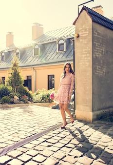 Mooie brunette vrouw met een boeket bloemen wandelen op straat in zonnestralen