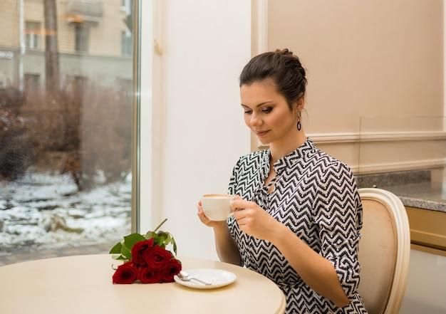 Mooie brunette vrouw met een kopje koffie en rozen zittend aan een tafel in een café