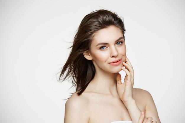 Mooie brunette vrouw met gezonde frisse huid en vliegend haar glimlachend aanraken gezicht.