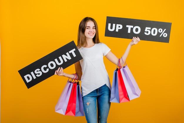 Mooie brunette vrouw met kleurrijke boodschappentassen en copyspace tekst korting 50% teken banner geïsoleerd over geel