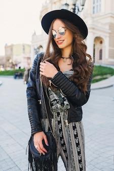 Mooie brunette vrouw met lang golvend kapsel in het voorjaar of najaar stijlvolle stedelijke outfit lopen op straat. rode lippen, slank lichaam. street fashion concept.