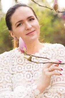 Mooie brunette vrouw met natuurlijke make-up poseren in de buurt van de bloeiende magnolia bloemen