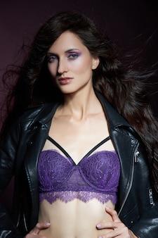 Mooie brunette vrouw met natuurlijke make-up poseren op donkere achtergrond. gladde tere gezichtshuid