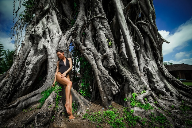 Mooie brunette vrouw met perfect lichaam in zwembroek in de buurt van de grote boom op bali