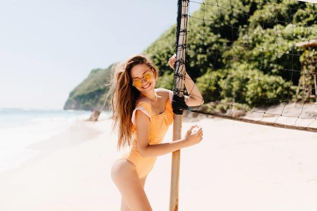 Mooie brunette vrouw met schattige glimlach aanraken volleybal ingesteld op strand. portret van prachtig gelooid meisje in zonnebril ontspannen op exotisch eiland.