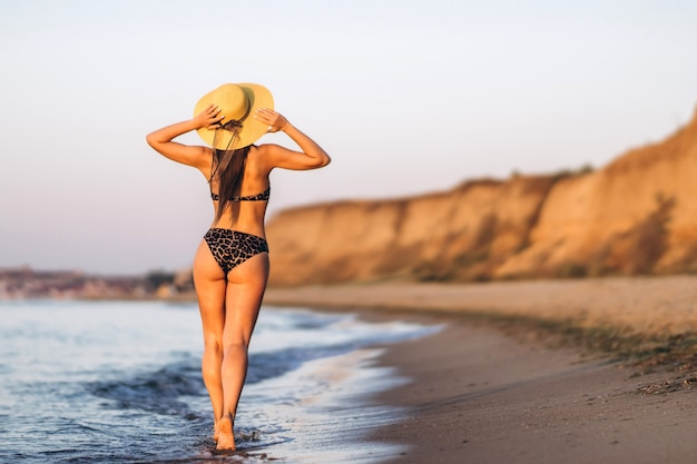 Mooie brunette vrouw ontspannen op het strand aan zee.