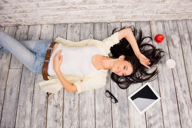 Mooie brunette vrouw op een houten vloer