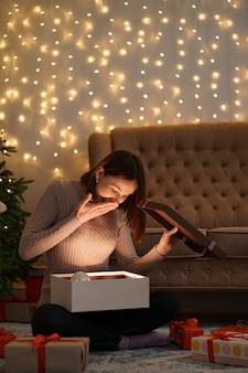 Mooie brunette vrouw opent een schattig cadeau met lichtjes