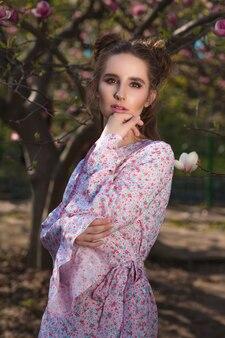 Mooie brunette vrouw poseren in de buurt van de bloeiende magnoliaboom in modieuze jurk