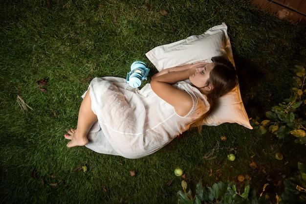 Mooie brunette vrouw slapen 's nachts tuin op kussen
