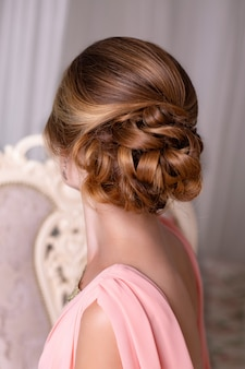 Mooie brunette vrouw terug met elegante bruiloft kapsel en bloemen
