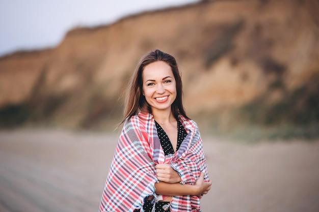 Mooie brunette vrouw wandelen op het strand bij zonsopgang gewikkeld in een warme deken.