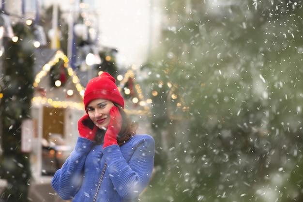 Mooie brunette vrouw wandelen op kerstmarkt tijdens de sneeuwval. ruimte voor tekst