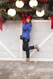 Mooie brunette vrouw wandelen op kerstmarkt tijdens de sneeuwval