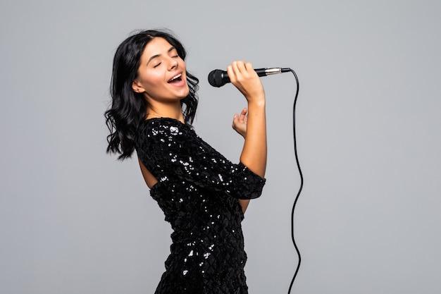 Mooie brunette vrouw zingen naar microfoon geïsoleerd op grijze muur