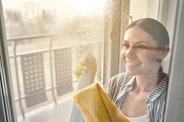 Mooie brunette vrouwelijke persoon die positiviteit uitdrukt tijdens het wassen van ramen in haar kamer