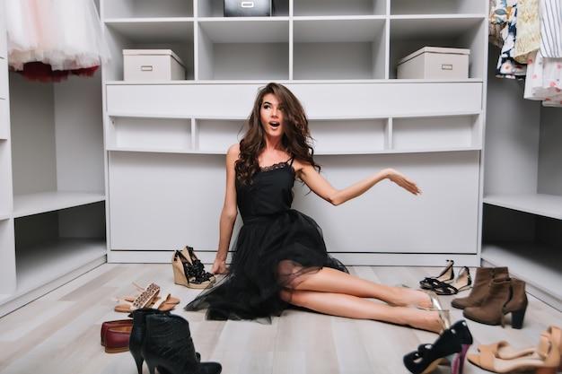 Mooie brunette zittend op de vloer in luxe kleedkamer rond schoenen, jonge vrouw denken wat te dragen. ze heeft een verbaasde, bedachtzame blik. zwarte jurk en zilveren schoenen aan.