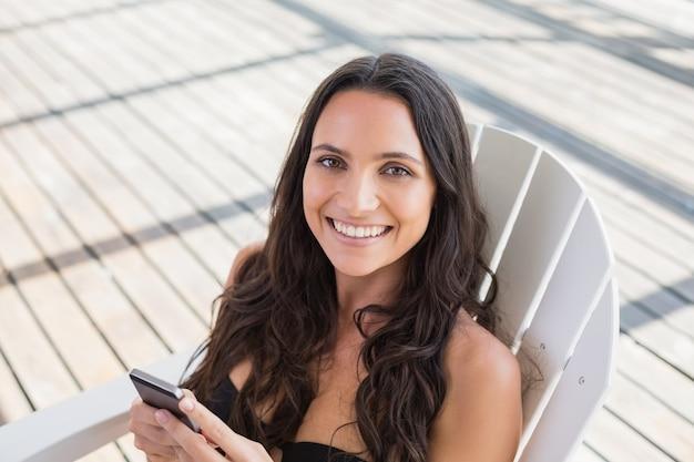 Mooie brunette zittend op een stoel en sms met haar mobiele telefoon