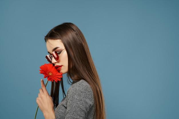 Mooie brunette zonnebril rode bloem in de buurt van gezicht cosmetica blauwe achtergrond