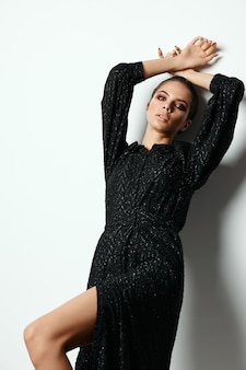 Mooie brunette zwarte jurk mode glamour geïsoleerde muur.