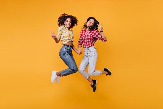 Mooie brunettes tonen teken van vrede. vrolijke meisjes poseren
