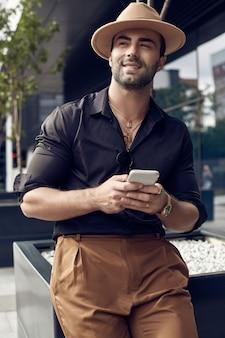 Mooie brutale gebruinde gespierde hipster man in zwart shirt en hoed met telefoon
