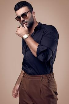 Mooie brutale gebruinde hipster man in een zwart shirt en een bril