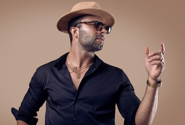 Mooie brutale gebruinde hipster man in een zwart shirt, hoed en bril