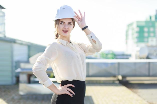 Mooie businesslady in witte blouse, horloge, helm en zwarte rok staan op het dak