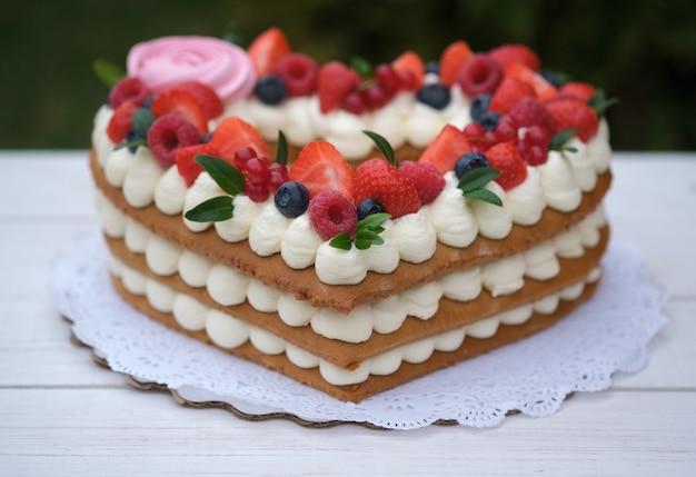 Mooie cake in de vorm van een hart met kaascrème en bessen