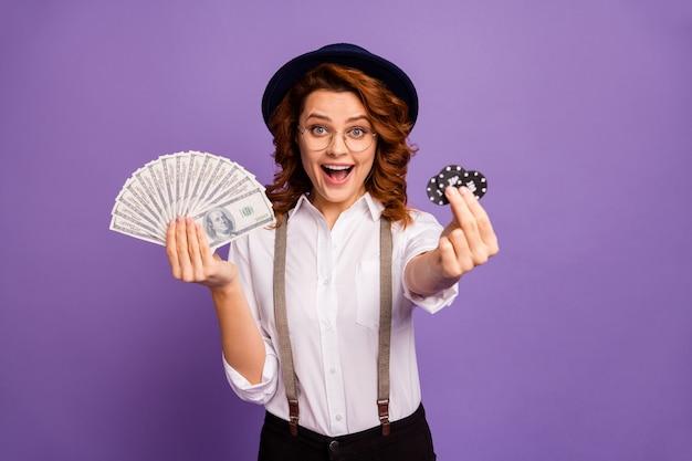 Mooie casinohandelaar die drie pokerfiches laat zien, houdt pakgeld vast